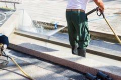 Arbeitskraftreinigungsboden mit Hochdruckwasserstrahl stockfotos