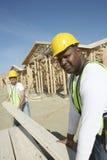 Arbeitskräfte, die Bretter an der Baustelle stapeln Stockfotos