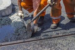 Arbeitskräfte, die eine Schaufel verwenden, um Gussasphalt zu verbreiten Stockfotos
