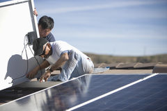 Arbeitskräfte, die Sonnenkollektor auf die Dach-Oberseite reparieren Stockbilder