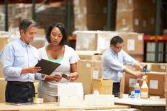 Arbeitskräfte im Lager, das Waren für Versand vorbereitet Stockfotografie