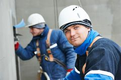 Arbeitskräfte am Vergipsen der Fassadenarbeit Lizenzfreies Stockbild