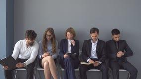 Arbeitslose erwarten die Interviews, die auf Stühlen in der Halle eines Bürogebäudes sitzen lizenzfreie stockfotografie