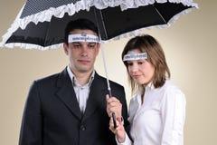 Arbeitslose Leute, die unter Regenschirm bleiben Stockfotografie