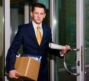 Arbeitsloser junger Manager, der Geschäftszentrum lässt stockfoto