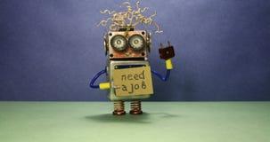 Arbeitsloser lustiger Roboter, der nach einem Job sucht Verrückter Spielzeugroboter spinnt eine Pappmitteilung, die handgeschrieb stock video footage
