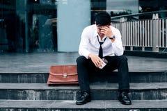 Arbeitsloser müder oder betonter Geschäftsmann, der auf dem Gehweg sitzt stockfotos