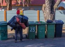 Arbeitsloser Mann, der durch Mülleimer sucht Stockfotografie