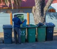 Arbeitsloser Mann, der durch Mülleimer sucht Lizenzfreie Stockfotos