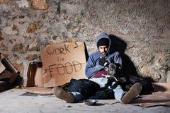 Arbeitsloser Mann mit dem Hund, sitzend nahe bei Almosen rollen lizenzfreies stockbild