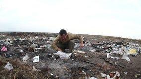 Arbeitsloser obdachloser schmutziger schauender Lebensmittelmann des Dumps stock video footage