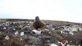 Arbeitsloses obdachloses schmutziges schauendes Mannlebensmittel des Dumps stock footage