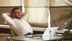 Arbeitspause im Büro Der Geschäftsmann lehnte sich zurück in seinem Stuhl, geplantscht Fernbeschäftigung, freiberuflich tätig stock video