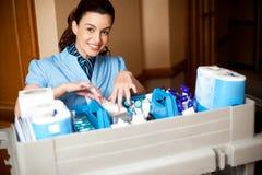 Arbeitspersonal, der Toilettenartikel in einem Radwagen anordnet Lizenzfreies Stockfoto