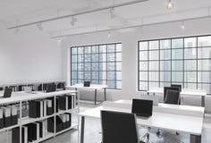 Arbeitsplätze in einem hellen modernen Büro des Dachbodenoffenen raumes Tabellen ausgerüstet mit Laptops; die Regale der Unterneh Stockfotografie