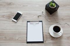 arbeitsplatz Auf dem Holztisch ist ein Ordner mit einem Klipp, ein Weiß Lizenzfreie Stockfotos