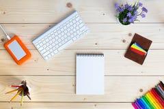 Arbeitsplatz auf gemütlichem hellem Holztisch mit Notizblock Stockfotos