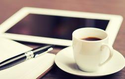 Arbeitsplatz, Büroschreibtisch: Kaffee und Tablette-PC und -notizbuch mit P Lizenzfreies Stockbild