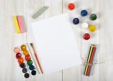 Arbeitsplatz des Designers mit farbigen Bleistiften, Bürste, Gouachegläsern, Aquarellfarben, Kreiden und einem Weißbuch in der Sp Lizenzfreies Stockfoto