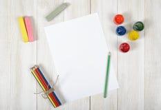 Arbeitsplatz des Designers mit farbigen Bleistiften, Bürste, Gouachegläsern, Kreiden und einem Weißbuch in der Draufsicht Stockbild