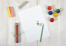 Arbeitsplatz des Designers mit farbigen Bleistiften, Bürste, Gouachegläsern, Kreiden und einem Weißbuch in der Draufsicht Stockfotos