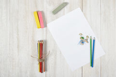 Arbeitsplatz des Designers mit farbigen Bleistiften, Bürste, Gouachegläsern, Kreiden und einem Weißbuch in der Draufsicht Stockfoto
