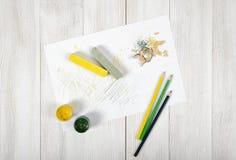 Arbeitsplatz des Designers mit farbigen Bleistiften, Bürste, Gouachegläsern, Kreiden und einem Weißbuch in der Draufsicht Lizenzfreie Stockbilder