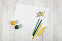 Arbeitsplatz des Designers mit farbigen Bleistiften, Bürste, Gouachegläsern, Kreiden und einem Weißbuch in der Draufsicht Lizenzfreie Stockfotos