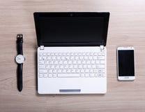 Arbeitsplatz - Draufsicht des weißen Laptops, des intelligenten Telefons und der Uhr auf t lizenzfreie stockbilder