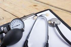 Arbeitsplatz eines Doktors Medizinisches Klemmbrett und Stethoskop auf hölzernem Schreibtischhintergrund Beschneidungspfad einges Lizenzfreie Stockbilder