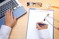 Arbeitsplatz eines Doktors Stethoskop und andere Sachen auf hölzernem De Lizenzfreies Stockbild
