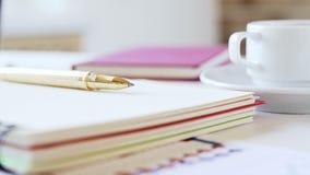 Arbeitsplatz eines Geschäftsmannes Notizbuch, Stift, Kaffeetasse und anderes Zubehör auf dem Schreibtisch stock video footage