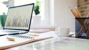 Arbeitsplatz eines Geschäftsmannes Schreibtisch mit einem Laptop, Tablette, Notizbuch und anderem Zubehör stock footage