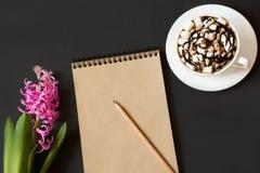 Arbeitsplatz für Blogger mit Notizbuch des Kraftpapiers, Bleistift, Tasse Kaffee, Blume auf schwarzem Hintergrund Bild mit Kopien Stockbilder