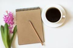 Arbeitsplatz für Blogger mit Notizbuch des Kraftpapiers, Bleistift, Tasse Kaffee, Blume auf weißem Hintergrund Bild mit Kopienrau Stockfotografie