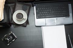 Arbeitsplatz für Kunst mit Notizbuch, Laptop, Kamera und Kaffee Lizenzfreie Stockbilder
