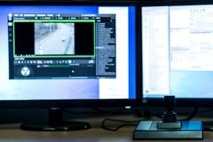 Arbeitsplatz für Videoüberwachung Unscharfe Monitoren auf den Hintergrund- und Steuerknüppelkontrollen im Vordergrund lizenzfreie stockfotos