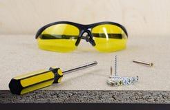 Arbeitsplatz, gelber Schraubenzieher und Gläser auf einem Holztisch stockbild