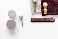 Arbeitsplatz im Friseursalon Rasiermesser, Rasierpinsel, Kamm auf weißem copyspace Draufsicht des Hintergrundes Lizenzfreie Stockfotos