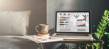 Arbeitsplatz im schlechten Raum ohne Leute, Nahaufnahme des Laptops mit Diagrammen, Diagramme, Diagramme auf Schirm auf Tabelle Lizenzfreie Stockfotos