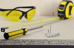 Arbeitsplatz, Maßband, gelber Schraubenzieher, Gläser und Schrauben am Holztisch lizenzfreies stockfoto