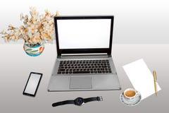 Arbeitsplatz mit der intelligenten weißem leerem Papier Telefon-Armbanduhr des Laptops und Stift mit dem Morgentee lokalisiert in Stockfotografie