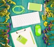 Arbeitsplatz mit drahtloser dünner Tastatur, grüne Maus, intelligentes Telefon, stockfotografie