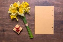 Arbeitsplatz mit einem Geschenk mit einem roten Band, einem Papier und Narzissen auf einem hölzernen Hintergrund Lizenzfreies Stockfoto