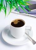 Arbeitsplatz mit Kaffee und einem Telefon Stockbild