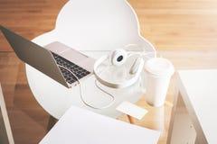 Arbeitsplatz mit Kaffee und Kopfhörern Lizenzfreie Stockfotografie