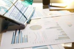 Arbeitsplatz mit Laptop, digitale Tablette; Diagramme im Büro stockfoto