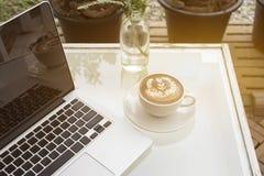 Arbeitsplatz mit Laptop und Kaffee auf Tabelle Stockbild