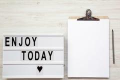 Arbeitsplatz mit noticepad, Bleistift und ` genießen heute ` Wort auf ligh lizenzfreies stockbild