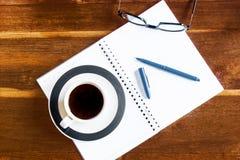 Arbeitsplatz mit Notizblock-, Kaffee- und Laptopgläsern Lizenzfreies Stockbild